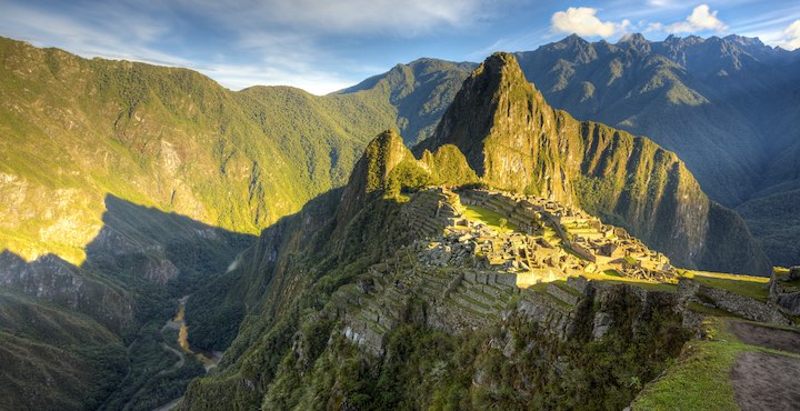 the sun shining on machu picchu in peru