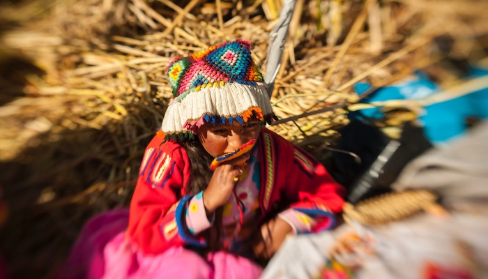 child on uros islands lake titicaca