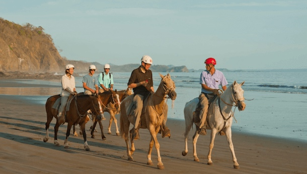 family horse riding on the beach in costa rica